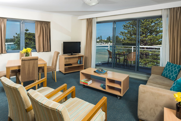 lounge area leading out to balcony with views of The Entrance ocean and Tuggerah Lake