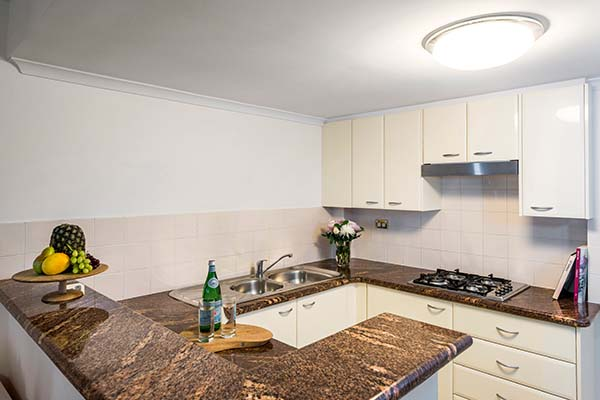 open plan kitchen in 1 bed hotel apartment Sydney cbd with marble top benches and stove top cooker
