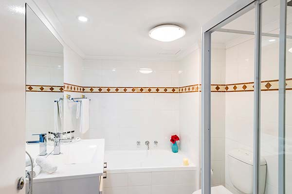 bathroom with shower and bath tub in 1 bed apartment at oaks on Castlereagh hotel in Sydney CBD
