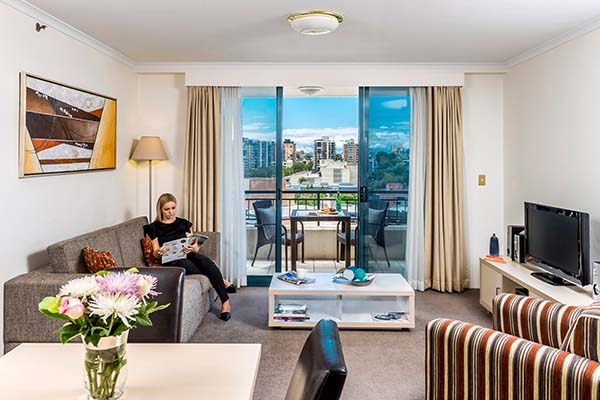business traveller reading magazine in hotel living room with television and balcony with views of Sydney city outside and outdoor furniture