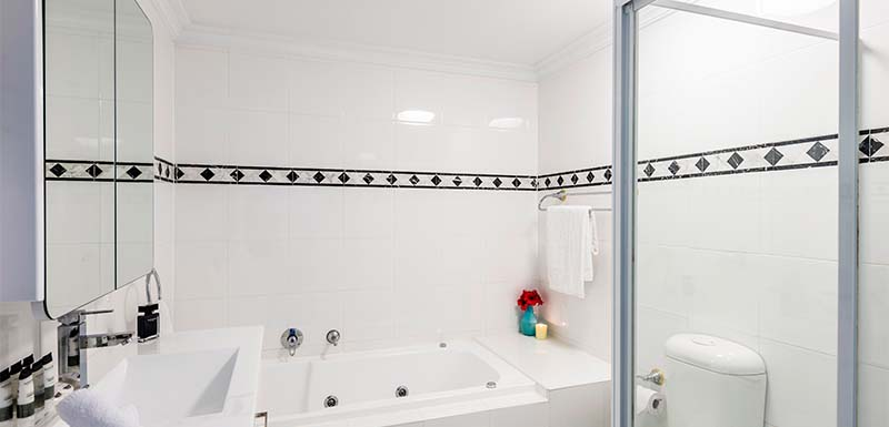 large en suite bathroom with mirror, bath, toilet and shower at Oaks on Castlereagh in Sydney CBD