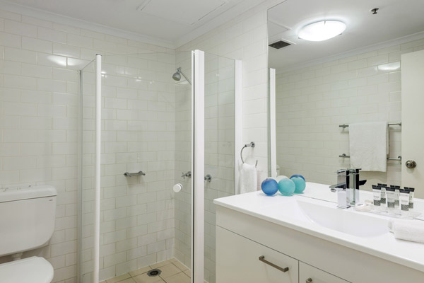 en suite bathroom in 2 bedroom apartment with toilet, clean towels and shower for hotel guests