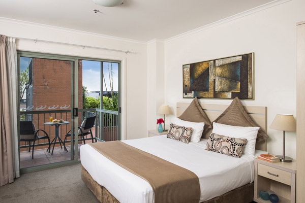 large bedroom in studio apartment with balcony at Oaks Goldsbrough Apartments hotel in Sydney