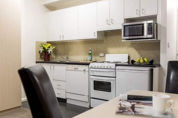 kitchen in studio apartment at Oaks Goldsbrough Apartments with microwave, oven and refrigerator