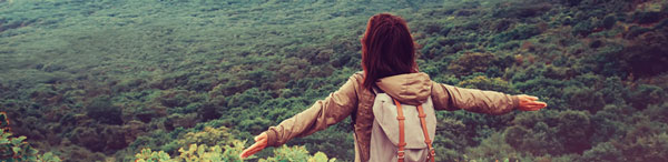Traveler with Backpack looking at New South Wales bushland with arms spread