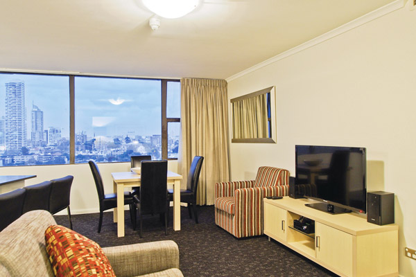 4 star, 2 bedroom apartment in Hyde Park hotel with flat screen TV, couches and view of Sydney city