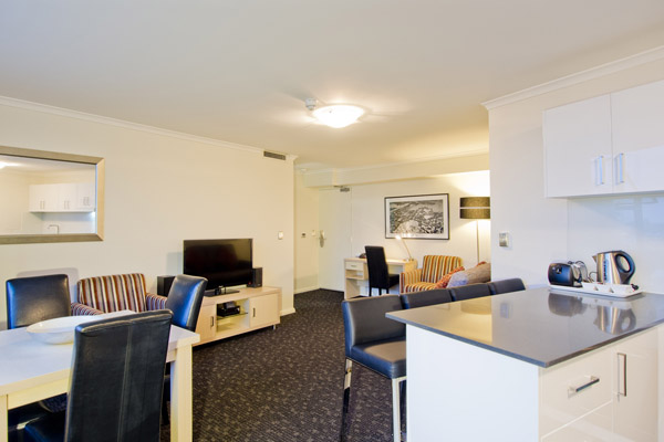 open plan kitchen and living room area in 2 bedroom hotel apartment in Hyde Park, Sydney city centre