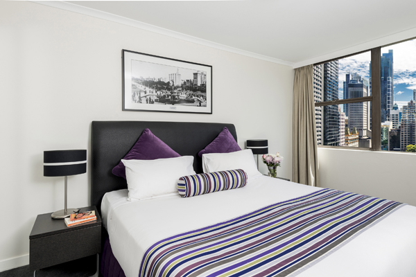 modern hotel bedroom in 2 bedroom apartment with views of Hyde Park in Sydney city