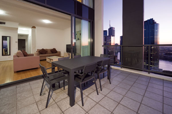 large balcony area with table and chairs and views of sun setting over Brisbane River and Story Bridge at Oaks 212 Margaret