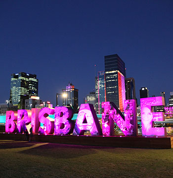 Brisbane sign illuminated at night with views of city in background across Brisbane River