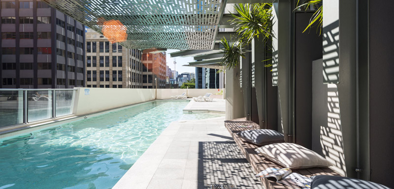 full length outdoor swimming pool at Oaks Aurora hotel in Brisbane city with sun loungers for guests to relax