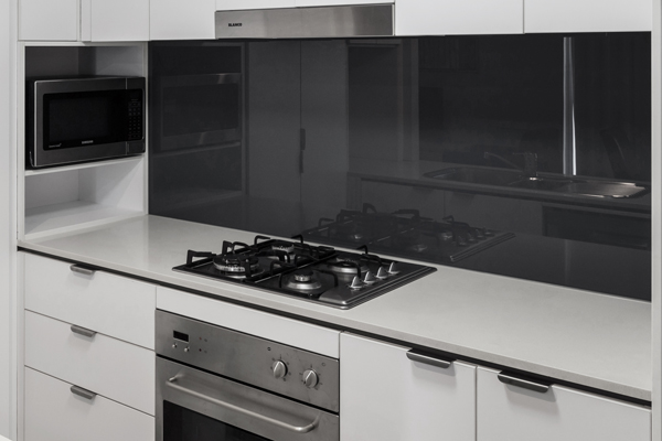 modern kitchen with microwave and stove tops in 1 bedroom apartment at Oaks Festival Towers hotel on Albert St in Brisbane city centre