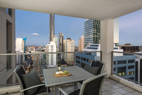 Hotels in Brisbane City Centre with 2 bedroom apartment balcony with view of Brisbane CBD sunset with wine, cheese and biscuits on table