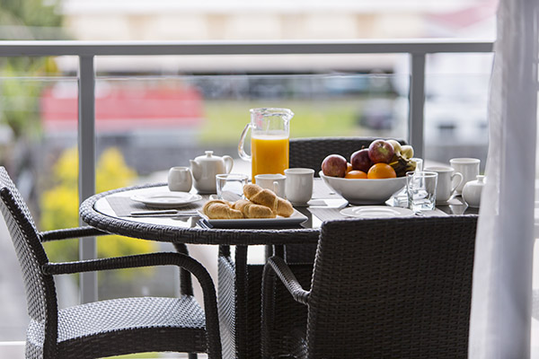healthy breakfast on table on balcony of 2 bedroom apartment at Oaks Carlyle hotel in Mackay