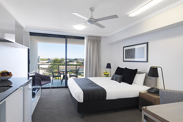 hotel room near Harbour Beach in Mackay with air con, queen size bed and balcony at Oaks Carlyle