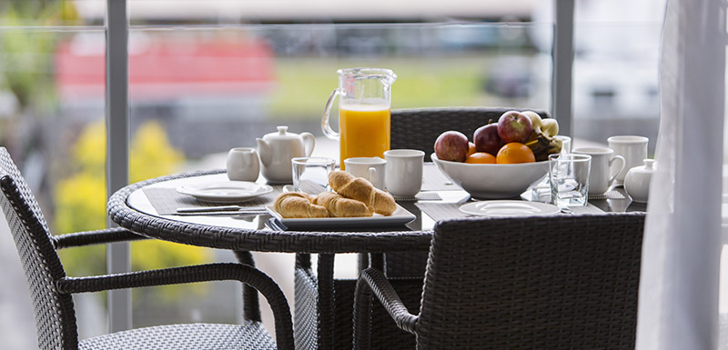healthy breakfast with fruit on table on balcony of 2 bedroom apartment at Oaks Carlyle hotel in Mackay