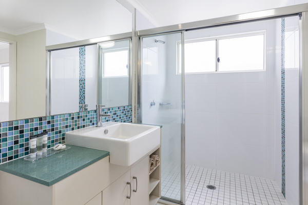 en suite bathroom with clean towels, large shower and big mirror in one bedroom apartment at Oaks Lagoons hotel in Port Douglas