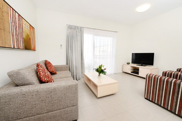 living room with TV, Foxtel, Wi-Fi and private balcony at Oaks Middlemount hotel near airport