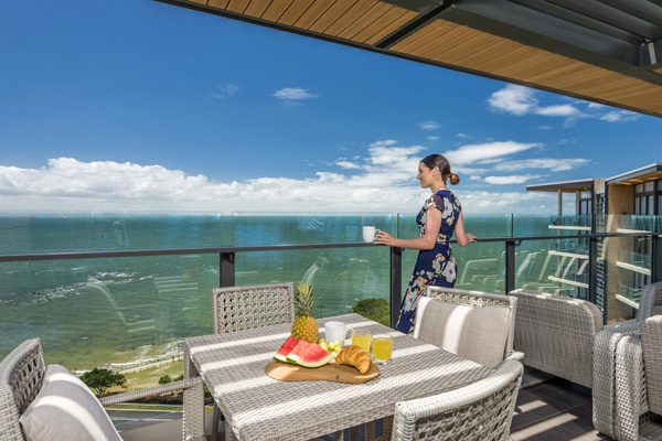 Woman standing on private balcony of 1 bedroom Redcliffe accommodation apartment looking at ocean nearby