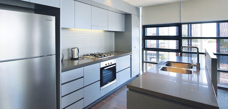 spacious kitchen with fridge, oven, kettle, microwave and toaster in 2 bedroom hotel accommodation at Mon Komo Hotel in Redcliffe