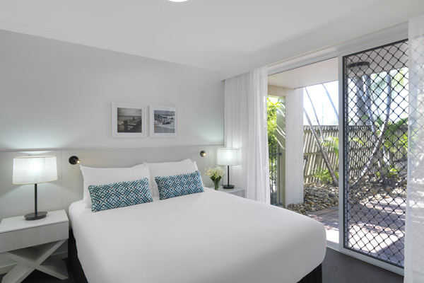 queen size bed in bedroom with sliding doors leading to private courtyard at Oaks Oasis Resort hotel in Caloundra, Sunshine Coast