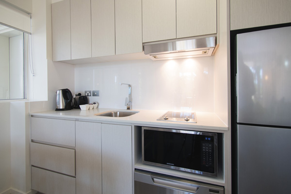 kitchen with microwave, large fridge, toaster and kettle in 2 bedroom apartment
