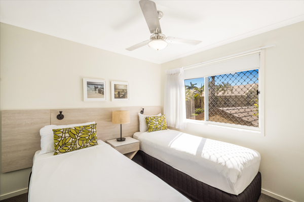 two single beds with clean sheets in 3 bedroom villa second bedroom with air con and ceiling fan at Oaks Oasis Resort hotel in Caloundra