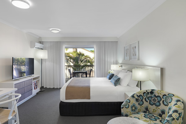 Caloundra accommodation with air conditioned master bedroom, TV and sliding glass doors leading out to private balcony of Executive Studio hotel apartment on Sunshine Coast