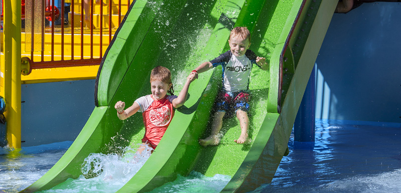 two children sliding down water slide, one of many things to do at Waterpark at Oaks Oasis Resort hotel in Caloundra on Sunshine Coast, Queensland, Australia