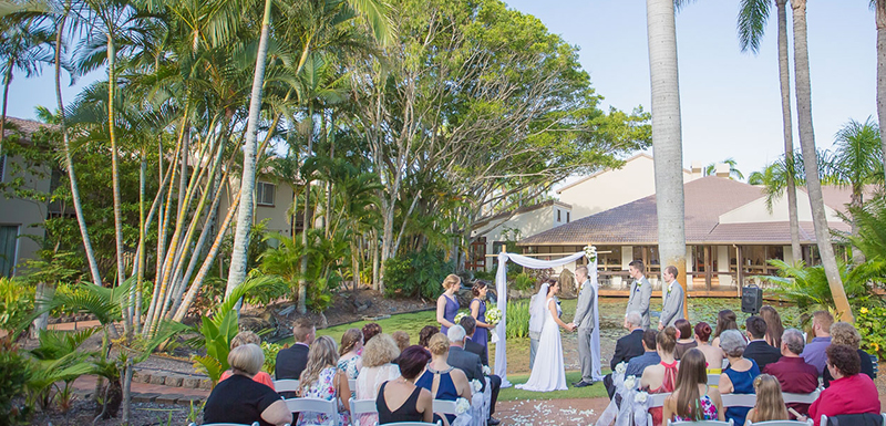 outdoor wedding ceremony with many guests and priest reading vows in Caloundra on Sunshine Coast, Queensland, Australia