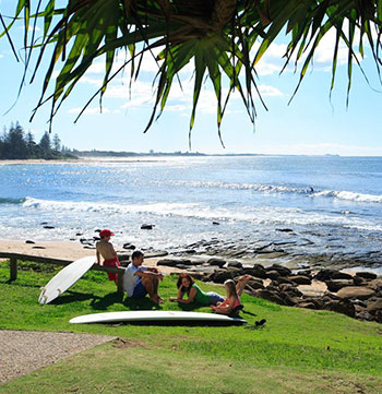 family relaxing on the beach with surfboards in Caloundra Sunshine Coast