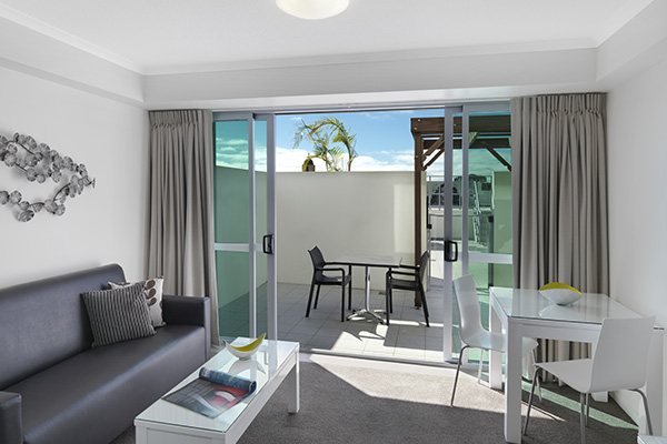 spacious living room area leading out to private balcony through glass sliding doors in 1 bedroom apartment at Oaks Rivermarque hotel in Mackay, Queensland, Australia