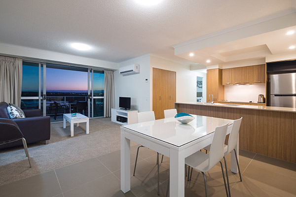 open plan living room with air conditioning, comfortable furniture and TV in two bedroom apartment at Oaks Rivermarque hotels in Mackay, Queensland, Australia