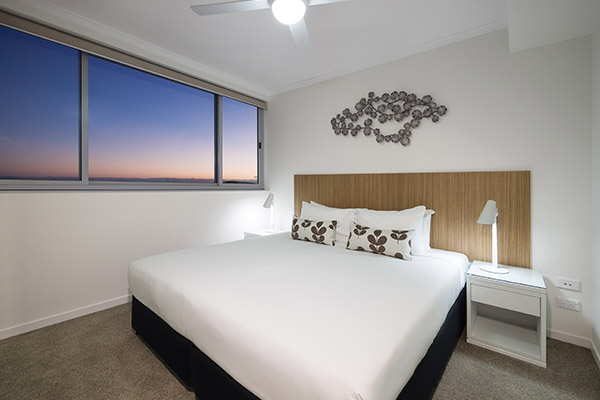 queen size bed in master bedroom of air conditioned two bedroom apartment with Wi-Fi