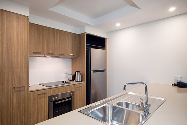 kitchen with full-size fridge, kettle, stove top plates, oven and toaster in two bedroom executive apartment for business travellers
