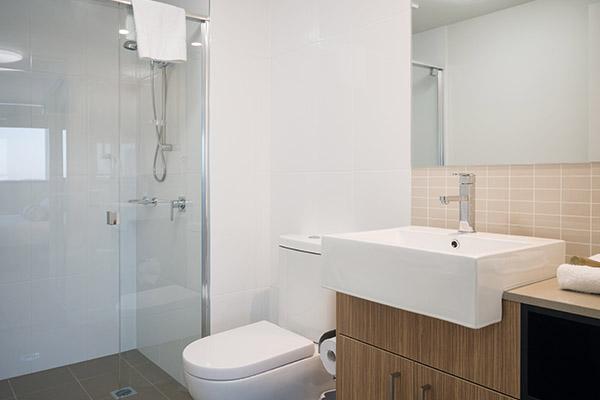 hotel room en suite bathroom with toilet, large shower and clean towels at Oaks Rivermarque in Mackay, Queensland, Australia