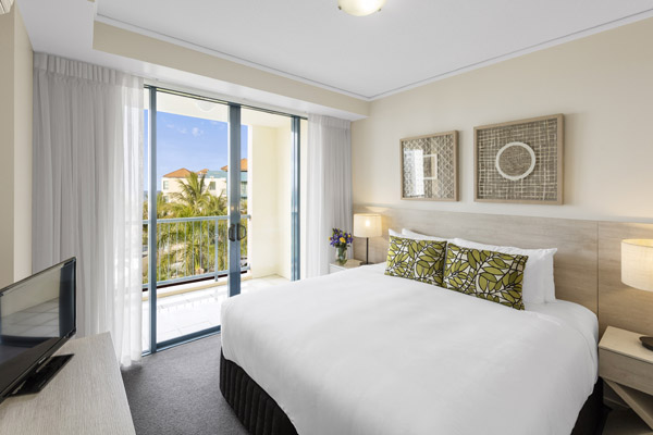 air conditioned bedroom with TV, Wi-Fi and private balcony with ocean views in one bedroom family apartment at Oaks Seaforth Resort hotel, Sunshine Coast, Queensland, Australia
