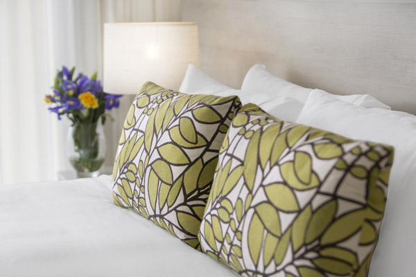 pillows on bed with flowers on side table in air conditioned 1 bedroom family apartment Oaks Seaforth Resort hotel, Sunshine Coast
