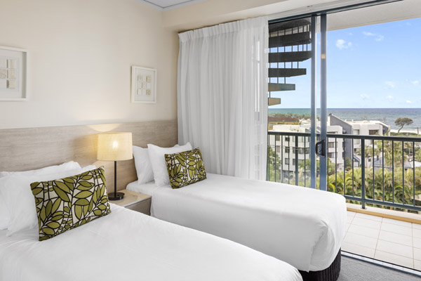 2 single beds in 2 bedroom penthouse apartment with air conditioning and private balcony views of ocean near beach at Oaks Seaforth Resort hotel, Alexandra Headlands, Sunshine Coast