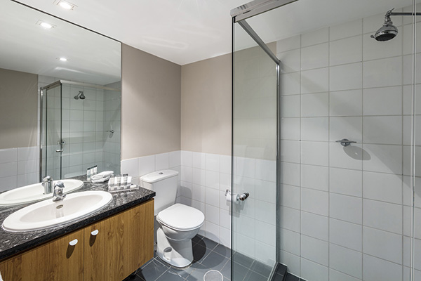 en suite bathroom with toilet, shower and large mirror in 2 bedroom deluxe apartment on North Terrace in Adelaide