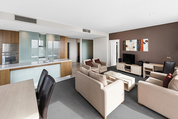 living room with modern furniture and TV in air conditioned 3 bedroom executive apartment near Adelaide Convention Centre