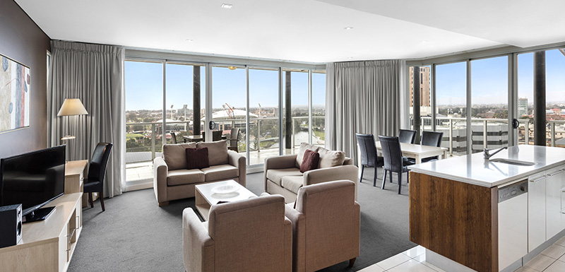 large living room with TV, Wi-Fi, air conditioning and kitchenette in hotel accommodation Adelaide CBD with big private balcony outside overlooking the Adelaide Oval
