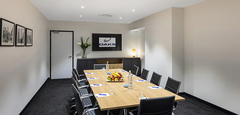 wooden table with comfortable black leather chairs in large conference room for hire in Adelaide CBD with big screen for presentations, lectern, podium and microphone for speakers