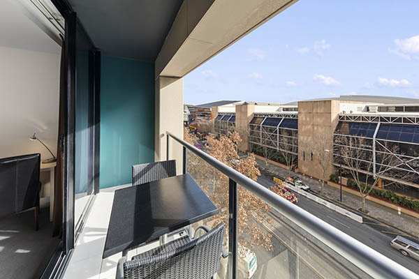 long, spacious private balcony with table, two chairs and views of Adelaide city
