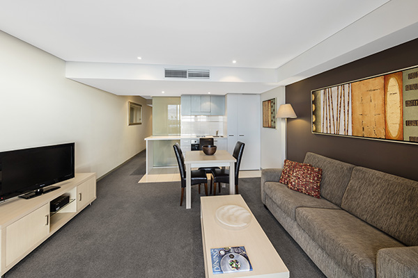 large living room with long comfortable couches, low tables, air conditioning unit, television with Foxtel and modern art on walls
