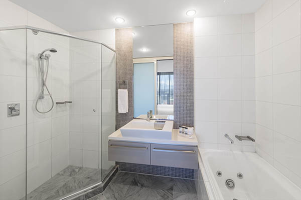 mirror, shower, bath tub and sink in en suite bathroom of 2 bedroom apartment near the Adelaide Oval