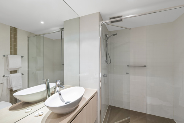 1 bedroom apartment en suite bathroom with clean towels, shower and large mirror at iStay Precinct hotel in Adelaide city