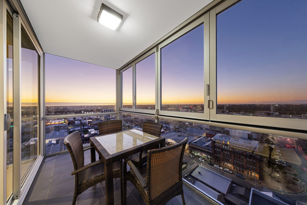 iStay Precinct hotel Adelaide CBD 2 bedroom apartment balcony with delicious vegetarian dinner off menu and views of Adelaide city centre at dusk
