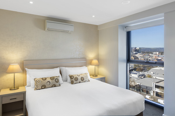 big bed with comfortable pillows and clean sheets in air conditioned 2 bedroom apartment with big window at iStay Precinct hotel in Adelaide city