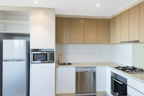 large kitchen with modern appliances, microwave, big refrigerator, freezer, oven and stove top hot plates